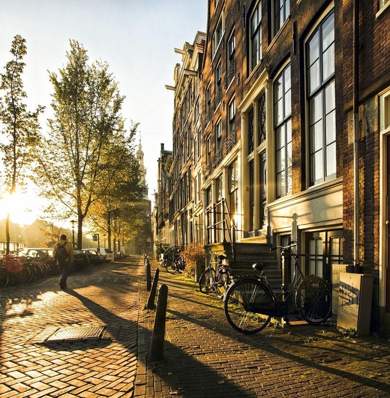 一个陌生人在阿姆斯特丹的街道上-伴随着长长的阴影-在这大气的日落中漫步在运河和住宅之间