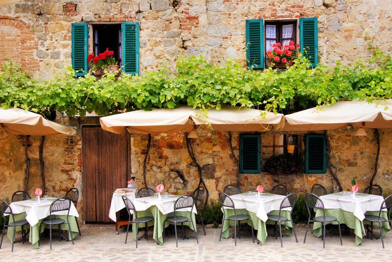 意大利托斯卡纳一座古色古香的石头建筑外的咖啡桌椅