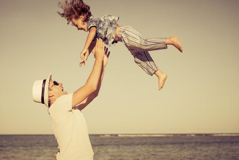 父亲和儿子白天在海滩上玩耍