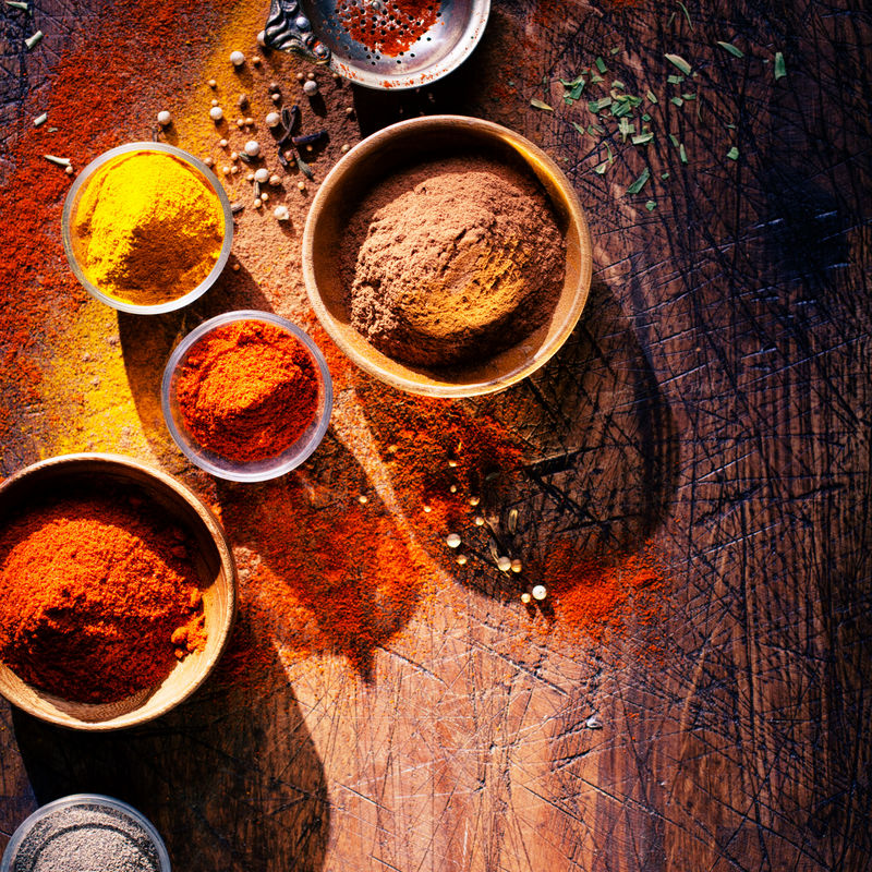 俯视图描绘了在一个乡村厨房里用香料烹饪-在一个有刻痕的旧木柜台上放着一碗五颜六色的香料和散粉