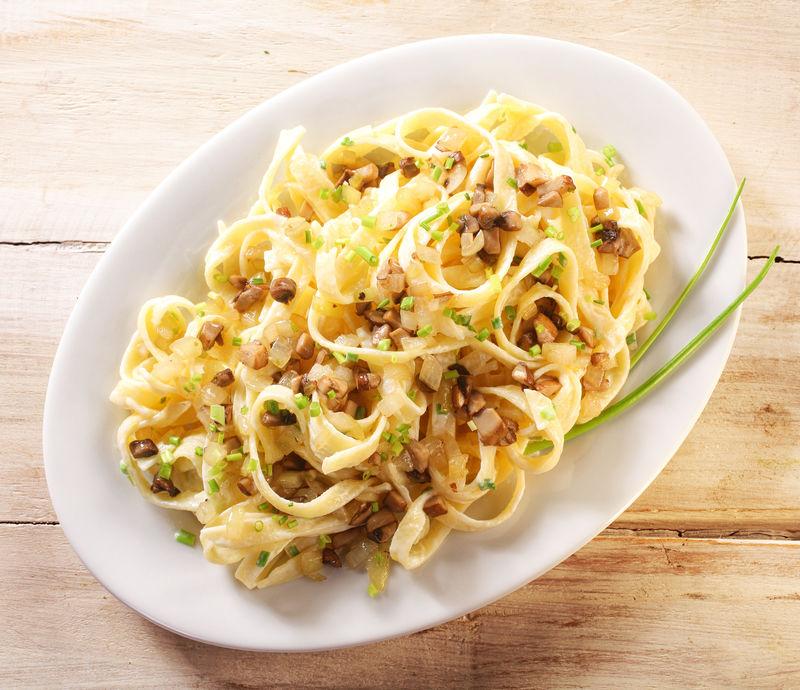 在一个白色的盘子上近距离观看新鲜制作的美味意大利面-放在一张木桌上