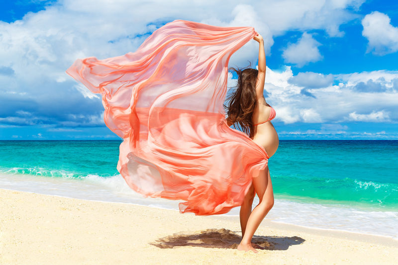 一位年轻的孕妇-穿着粉红色的衣服-在热带海滩上迎风飘扬-户外-健康怀孕-《自然》中的快乐孕妇-新生活理念