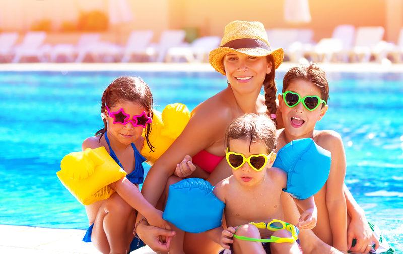 快乐的大家庭在泳池里玩-一起度过暑假-戴着有趣的彩色太阳镜-享受快乐的概念