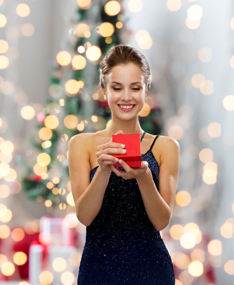 节日、庆祝活动和人们的观念-微笑的女人穿着衣服-在圣诞树灯的背景上拿着红色的礼品盒