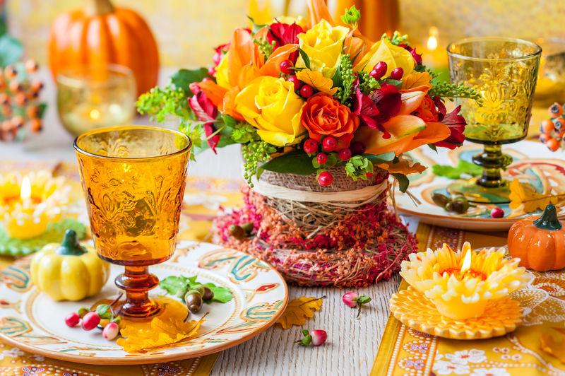 盛开秋花、蜡烛和南瓜的节日餐桌