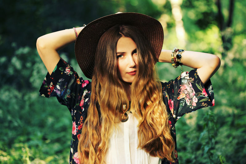 美丽的嬉皮士年轻女子的时尚肖像-穿着波西米亚时尚的衣服-戴着夏季的户外帽子-柔软温暖的复古色调-艺术的波西米亚风格