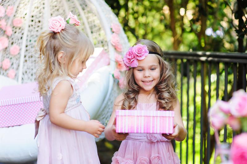 小孩给她的朋友一个生日礼物盒
