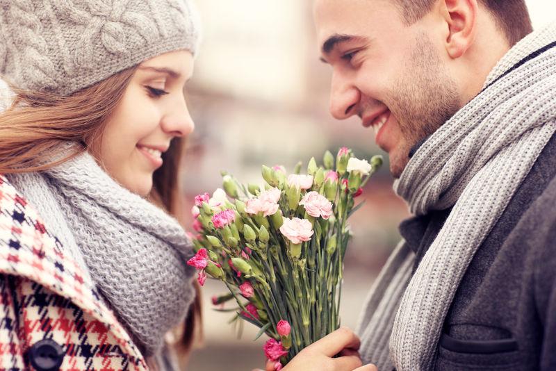 一个男人在冬天给他的情人献花的照片
