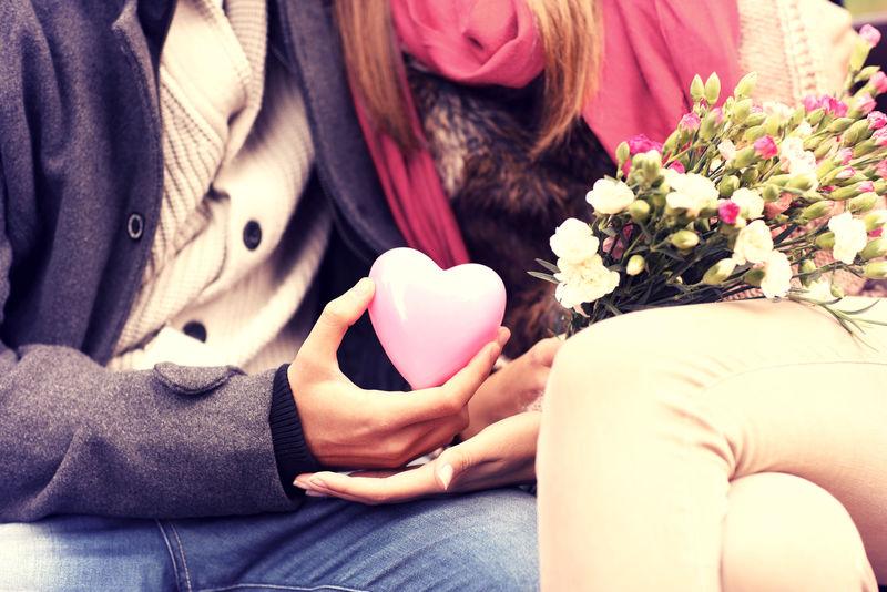 一对情侣坐在公园的长椅上-手里拿着情人节礼物和鲜花