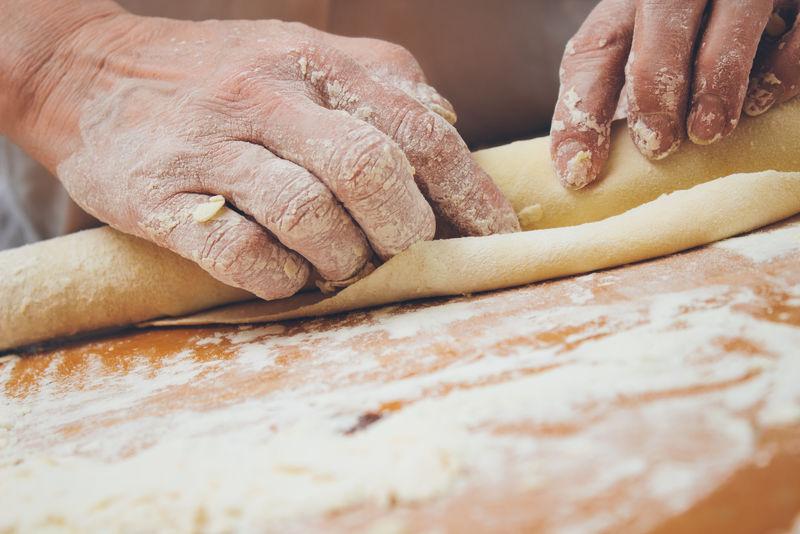 面包师用擀面杖捏面团的特写照片-复古风格的图像-添加的谷物