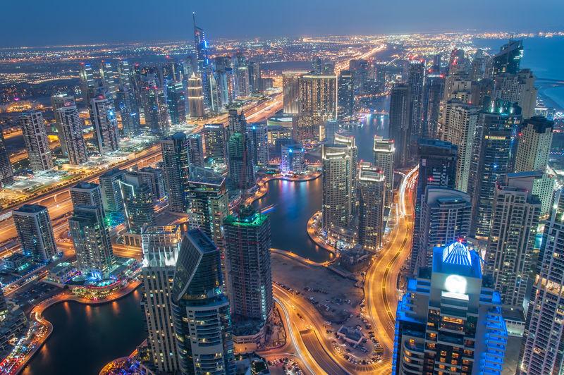迪拜码头和朱美拉湖的塔在蓝色的时刻-晴朗的夜晚-蓝蓝的天空闪烁着灯光和最高的摩天大楼