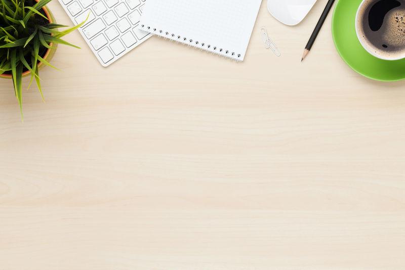 带记事本、电脑和咖啡杯的办公桌-使用复制空间从上方查看