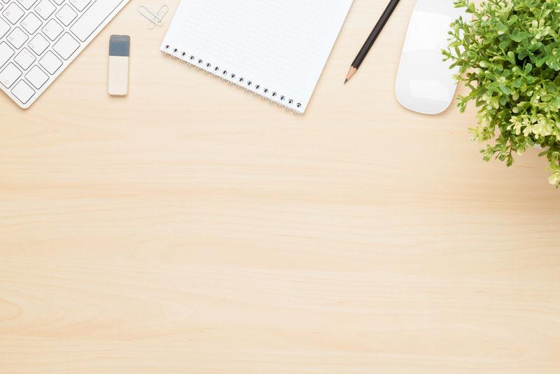 带记事本、电脑和鲜花的办公桌-使用复制空间从上方查看