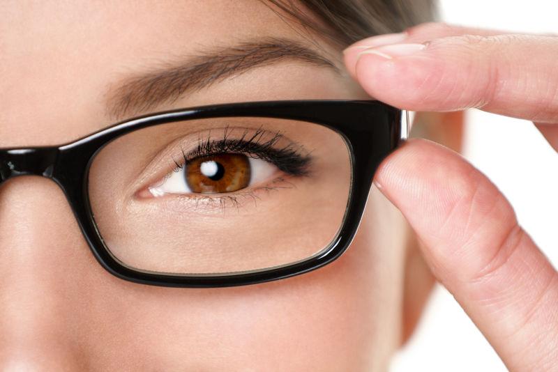 眼镜眼镜紧闭的女人抱着眼镜架微笑着开心-美丽的年轻混血白人/亚裔中国妇女戴黑色眼镜