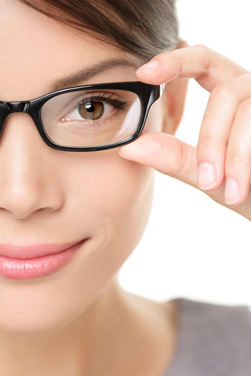 戴眼镜的女人特写肖像-戴眼镜的妇女特写镜头中拿着镜框-白人背景下美丽的年轻混血白人/亚裔华裔女性模特