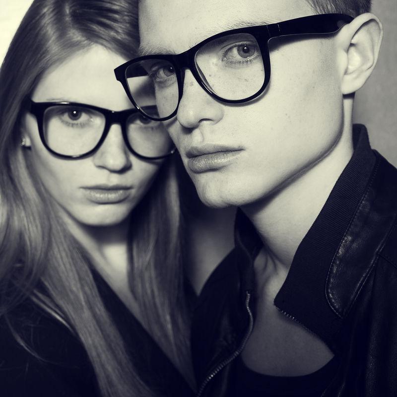眼镜的概念-金发碧眼的时尚双胞胎-穿着黑色的衣服-戴着时髦的眼镜-在灰色背景下合影-完美的肌肤-时尚风格-闭合.工作室拍摄