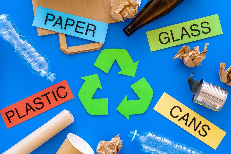 适用于绿色循环生态符号附近循环使用的材料-文字纸、玻璃、塑料、蓝色背景的罐子俯视图