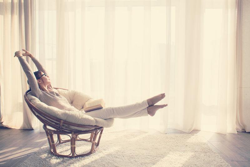 年轻的女人在家里坐在现代椅子在窗前她在客厅看书放松-Instagram调色