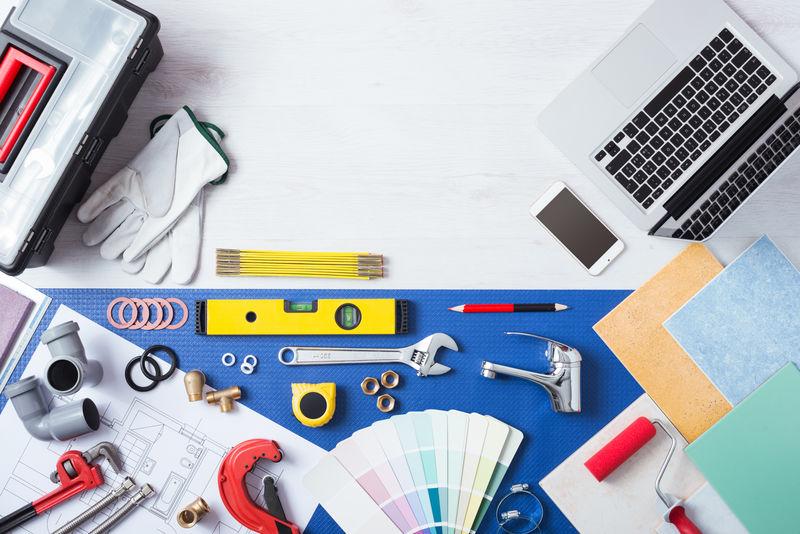 笔记本电脑放在木制桌子上-旁边是水管作业工具、瓷砖、水龙头和彩色样本俯视图、在线水管服务概念图