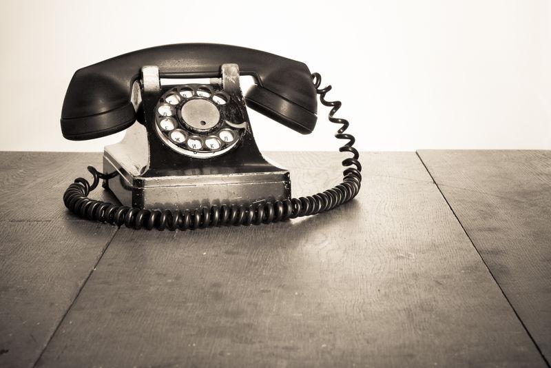 旧桌子上的老式电话-深褐色照片