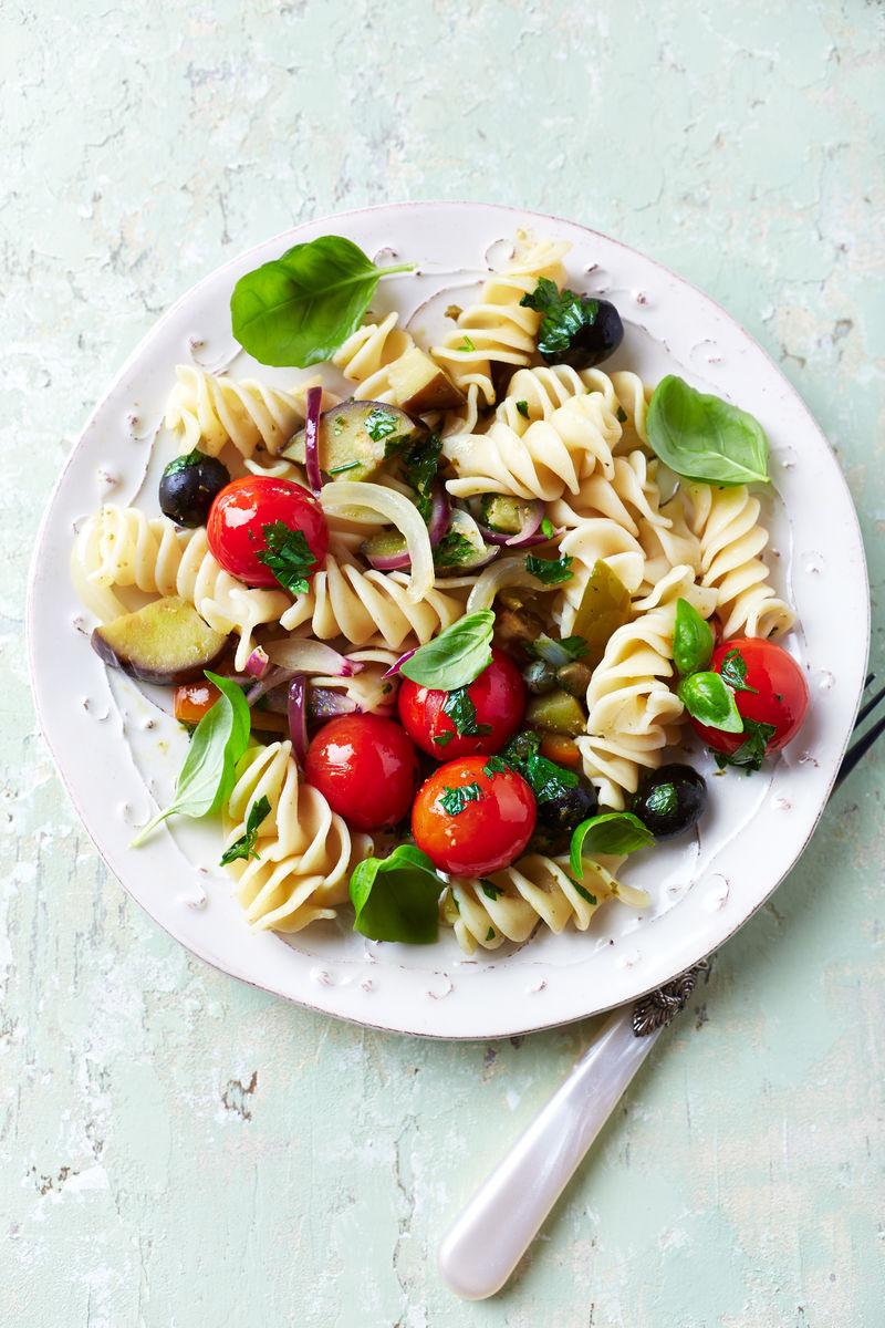 带有烤蔬菜和橄榄的乡村面食-富西洛尼意大利面配樱桃番茄、红洋葱、黑橄榄、茄子、新鲜欧芹和罗勒口味的意大利菜-质朴的木质背景-顶视图