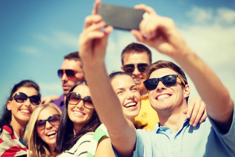 夏天-假期-假期和幸福概念的朋友采取selfie与智能手机组