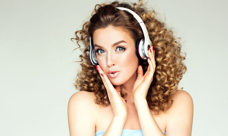 美丽的微笑女孩,卷发,听音乐。戴着大耳机的快乐女人享受生活。非洲式蓬松发型