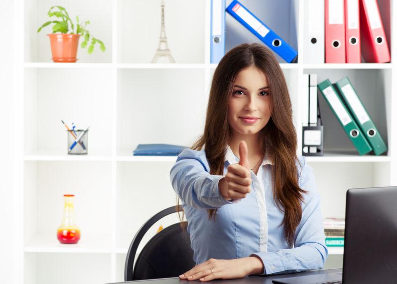 年轻成功的女性房地产专家大拇指出现-商业成功的概念-微笑的女专家坐在办公室的桌子旁