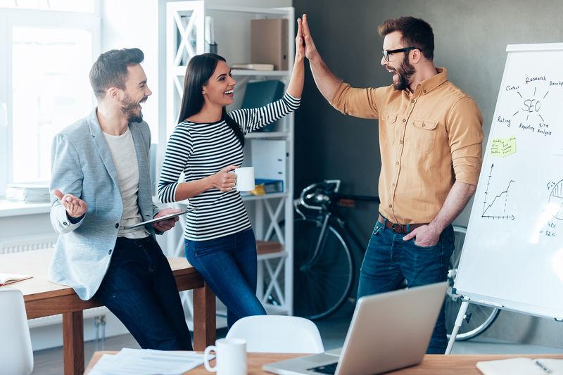 庆祝成功。快乐的年轻人站在办公室的白板旁,向同事们献上高五分。