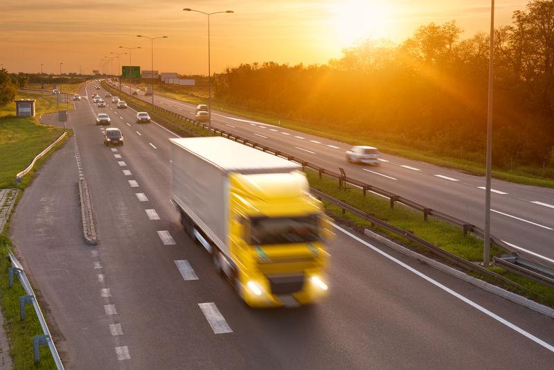 黄昏时分高速公路上高峰时段的黄色卡车