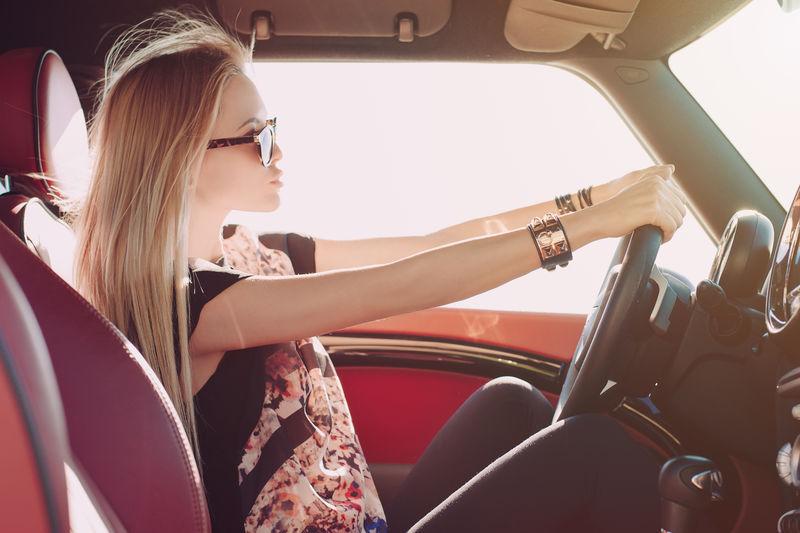 金发女郎坐在红色内饰的跑车车轮上-戴着黑色太阳镜-带金属嵌件的皮臂膀-双手放在车轮上-坐在一旁看着路面