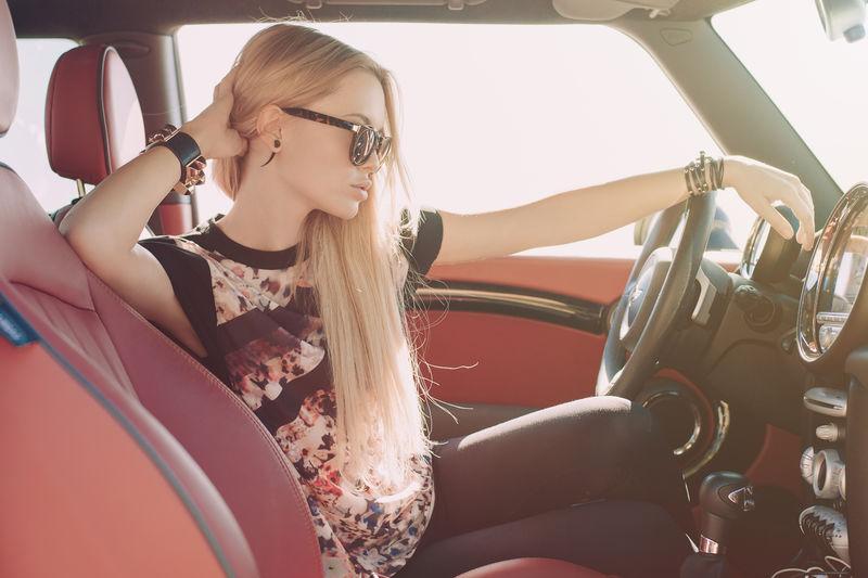 金发女郎坐在红色内饰的跑车车轮上-戴着黑色太阳镜-戴着带金属镶嵌件的皮革臂膀-手放在头旁-看着路面