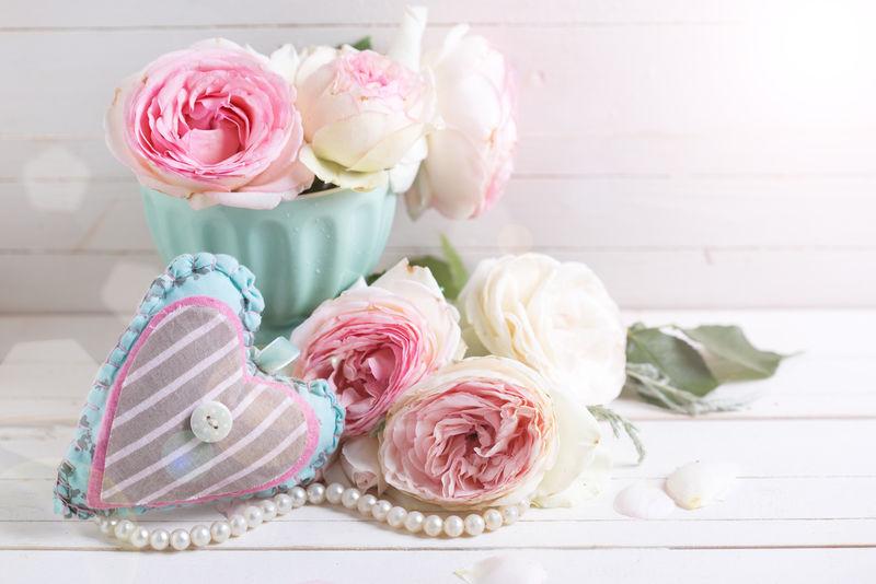 背景是粉红玫瑰的花朵和装饰性的心形-背景是白色的木漆-选择性聚焦