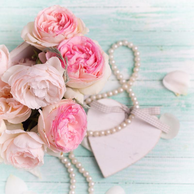木盆里的粉红玫瑰、装饰性的心形图案和绿松石背景上的珍珠-选择性聚焦-方形图像