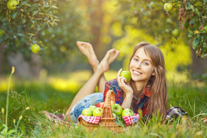 花园里有苹果的女人-一位年轻迷人的女士正躺在苹果园的草地上-微笑着-篮子里装满了成熟的红绿苹果-收获季节-乡村生活方式