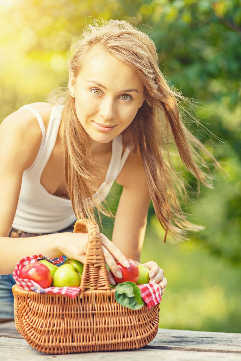 花园里有苹果的女人-一位年轻迷人的女士坐在苹果园的草地上-满篮成熟的红绿苹果-收获季节-乡村生活方式