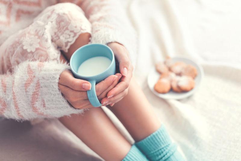 柔软的照片-女人在床上-手里拿着一杯牛奶-俯视图-舒适、舒适、柔软