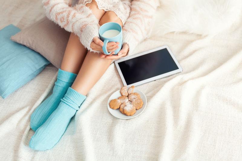 柔软的照片上的女人躺在床上-手里拿着药片和牛奶杯-俯视图-舒适、舒适、柔软