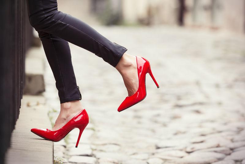 老妇人穿黑色皮裤子和红色高跟鞋