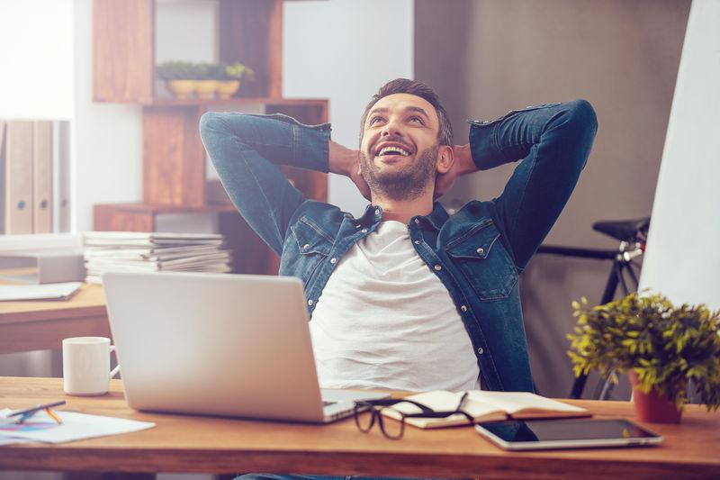 对完成的工作感到满意。快乐的年轻人坐在办公室工作的地方,一边在笔记本电脑上工作