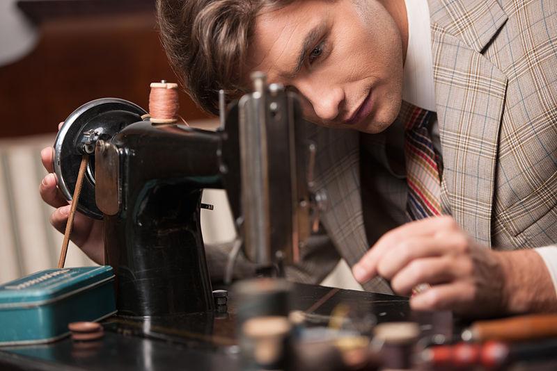 在工作中做裁缝-自信的年轻裁缝在裁缝店缝纫衣服