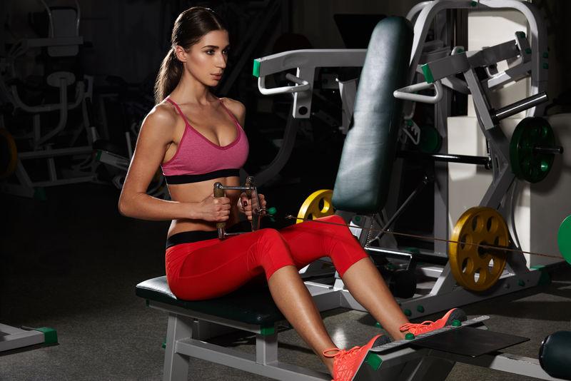 青年健身女子在健身房用健身器材进行运动