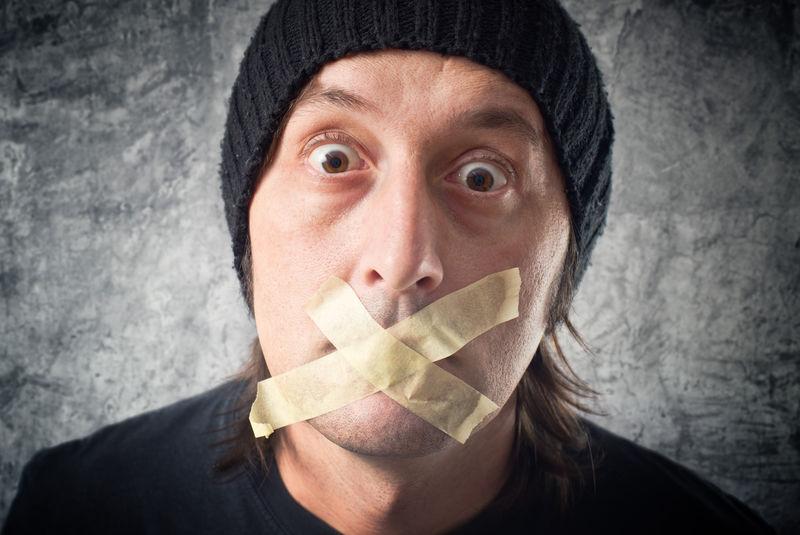 审查概念-我的嘴是密封的-一个戴黑帽子-嘴上贴着胶带的休闲男人