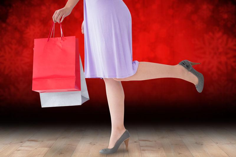 半身女装的女人拿着购物袋贴在地板上的雪花墙纸上