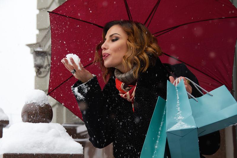 漂亮性感的年轻女子-棕色卷发-浓妆艳抹-身穿黑色外套-在白雪覆盖的街道上走过商店-带着红色雨伞和圣诞和新年冬季的礼品包