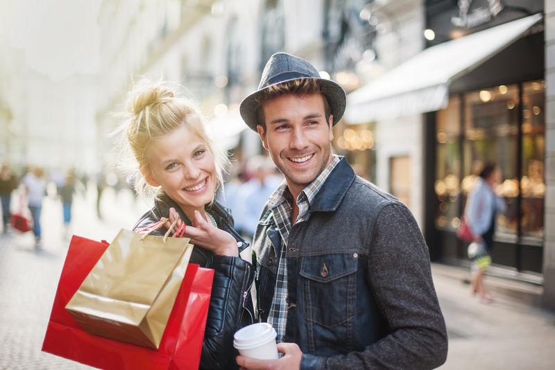 圣诞节期间-一对时髦的年轻夫妇在城里散步-年轻的女人穿着皮夹克-胳膊上挎着购物袋-男人手里拿着一杯咖啡
