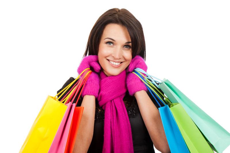冬天购物的女人开心地微笑着拿着白色背景隔离的袋子