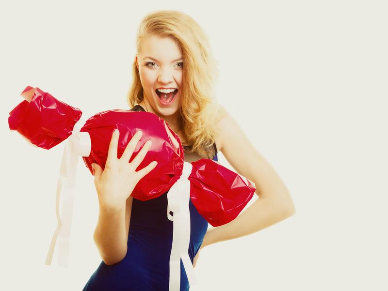 人们欢度佳节-爱与幸福的理念-微笑女孩手拿大红礼物糖果形隔离