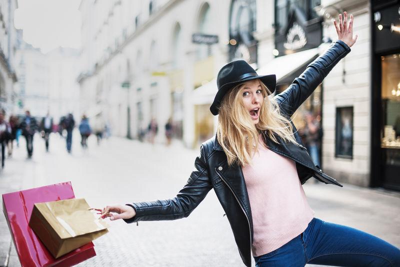 一位年轻时髦的妇女在城里购物-她用欢笑来表达自己的快乐