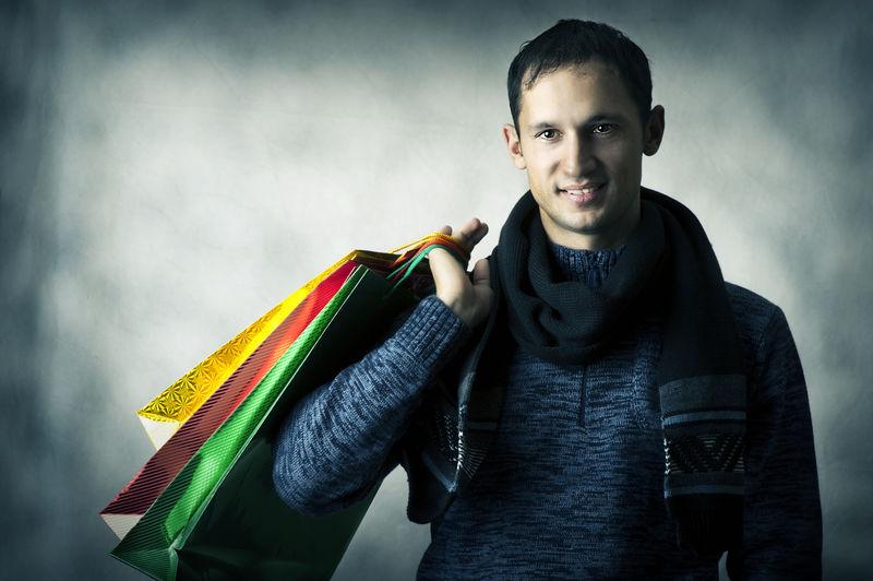 一个年轻人拿着包购物后戴着围巾和深蓝色衬衫的画像